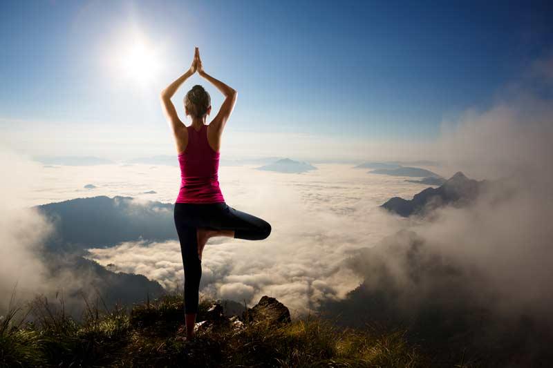 Girl doing yoga on a mountain