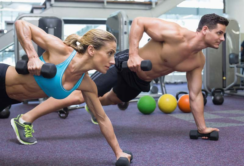 Two people working with weights in the gym