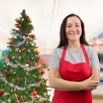 Store assistant in front of Christmas tree
